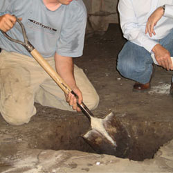 Digging a hole for the engineered fill used in a crawl space support system installation in Goshen