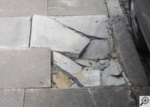 photo of a sinking concrete sidewalk with cracks in Columbia City