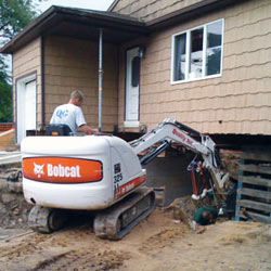 Excavating to expose the foundation walls and footings for a replacement job in Portage