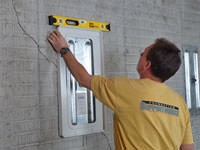 Positioning a wall plate cover on a foundation wall in Goshen.